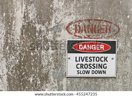 red, black and white Danger, Livestock Crossing, Slow Down warning sign - stock photo