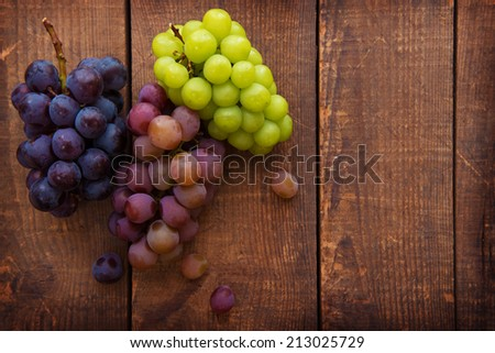 Red, black and white (green) grapes on a wooden table. Focus is on the grapes - stock photo