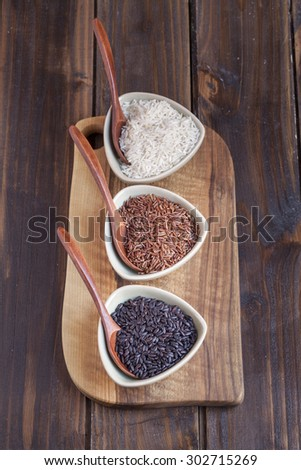 Red, black and white rice in bowls - stock photo