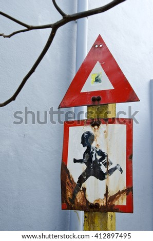 red, black and white roadsign in city street near school with a running child, India - stock photo