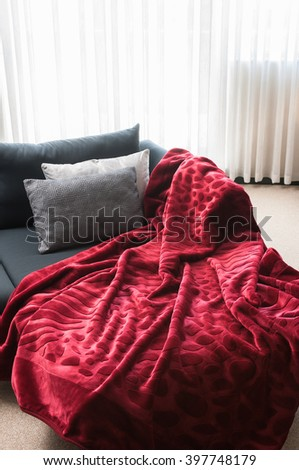 red blanket armchair with pillow and curtain - stock photo