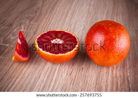 red blood sicilian orange whole, half and wedge on wooden background - stock photo