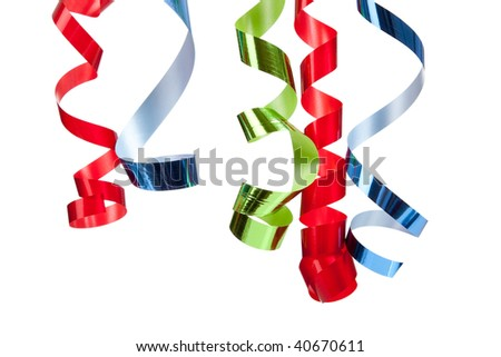 Red, blue and green curly ribbon hanging in front of a white background - stock photo