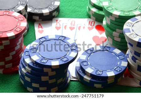 Red, blue, green, white and black poker chips and royal flush on green table - stock photo