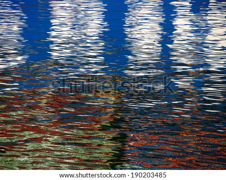 Red Blue white Color pattern shimmers and reflects in ripples of water making a psychedelic pattern. - stock photo