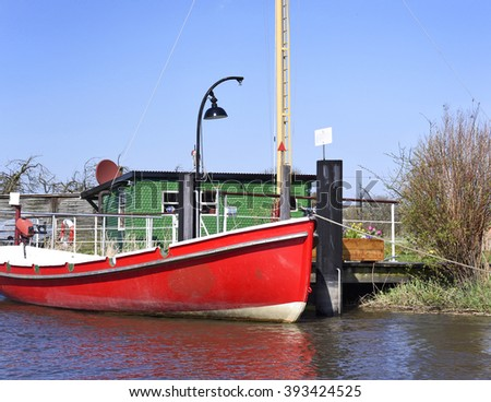 Red boat anchored on a wooden jetty or pier. River in springtime with red motorboat at a pier.  - stock photo