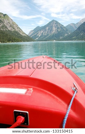 red boat in an alpine lake - stock photo