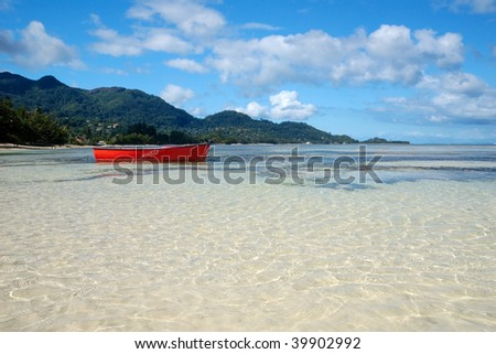 Red Boat in transparent waters - stock photo