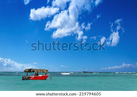 Red boat on azure water of Caribbean Sea - stock photo