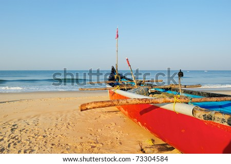 Red boat with fishing net on sandy shore - stock photo