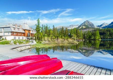 Red boats on the pier near Strbske Pleso lake, Slovakia - stock photo