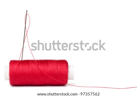 red bobbins of thread and needle isolated on white background