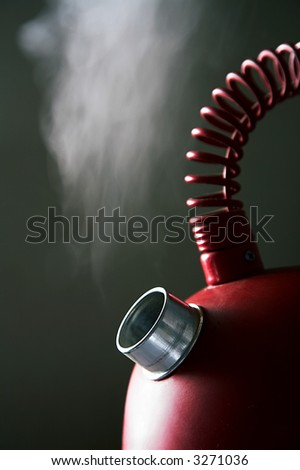Red boiling teapot on a dark background - stock photo