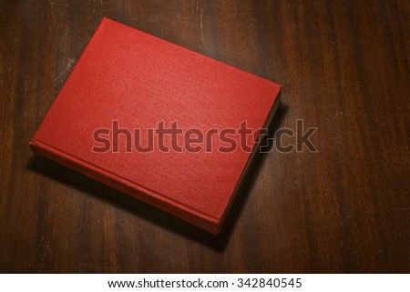 Red book on the wooden scratched table