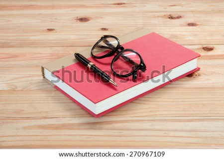 red book with glasses and pen on the wooden  - stock photo