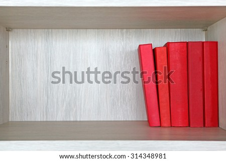 Red books in a wooden shelf. - stock photo