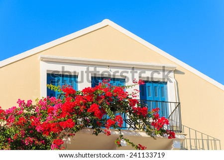 Red Bougainvillea flowers on balcony of typical Greek house in Fiskardo town, Kefalonia island, Greece - stock photo