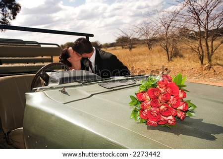 Red bouquet of roses on the bonnet of a car, just married bridal couple kissing in the background. Focus on Flowers