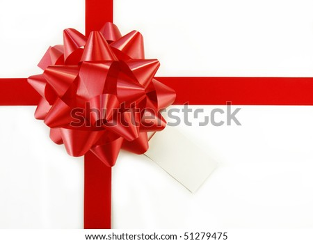 Red bow and ribbon on white gift box with tag. - stock photo