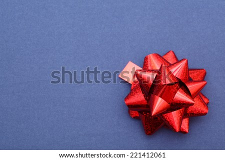 Red bow on blue paper background. Closeup. - stock photo