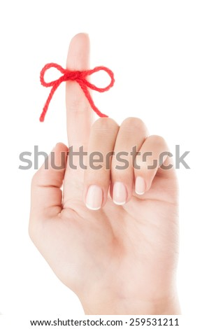 Red bow on finger isolated on white background. - stock photo