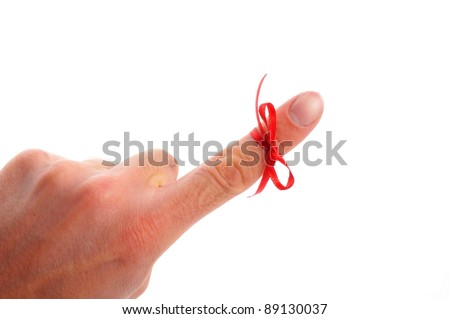 red bow on male finger showing reminder or dont forget concept in white - stock photo