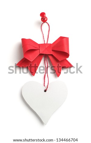 Red bow with a heart made of paper on white