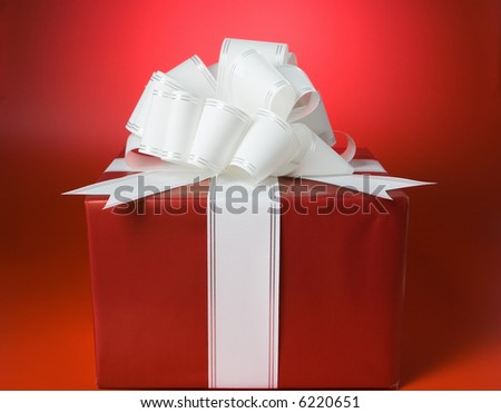 red box gift with ribbon and bow on red background
