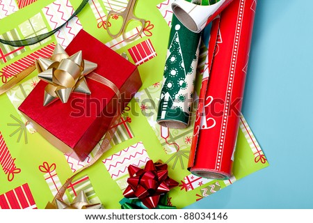 Red box with a gold bow and wrapping paper in the background