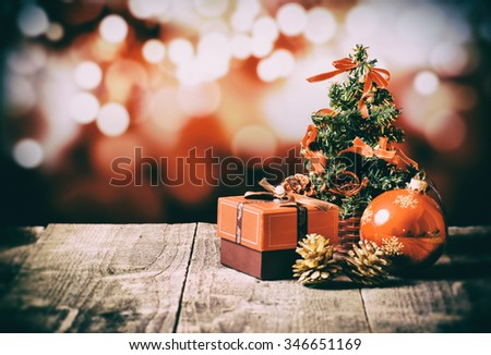Red box with bow, little Christmas tree, glass toy, pine cones, on old wood table and red background.  Cross processed image for vintage look - stock photo