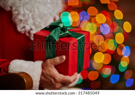 Red box with Christmas gift in Santa hands - stock photo