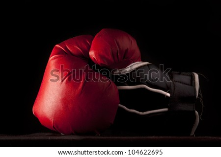 Red boxing glove on black close up with copy space - stock photo