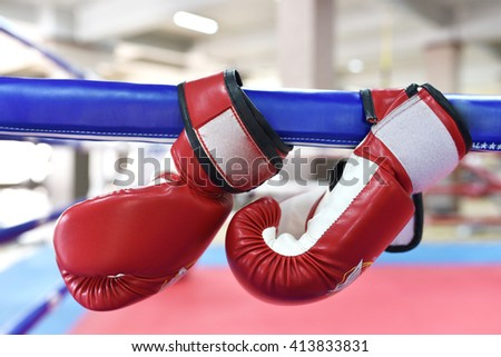 red boxing gloves hang on boxing ring  - stock photo