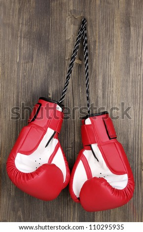 Red boxing gloves hanging on wooden background