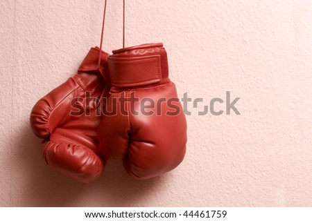 Red boxing gloves hanging over wall. - stock photo