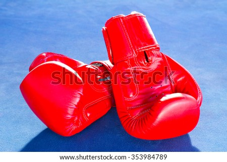 Red boxing gloves isolated on blue exercise mat. - stock photo