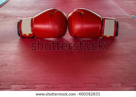 Red boxing gloves On Red rubber flooring - stock photo