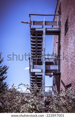 Red brick and concrete office building, with a rusty fire escape. Abandoned and derelict under a blue sky. - stock photo