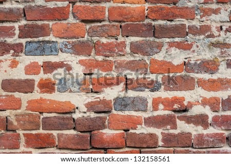 Red brick background: closeup of an old uneven brick wall. - stock photo