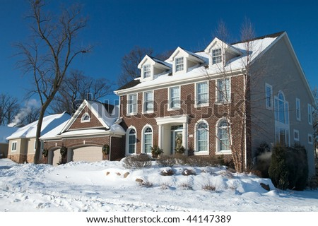Red Brick Colonial Home in the Winter Snow - stock photo