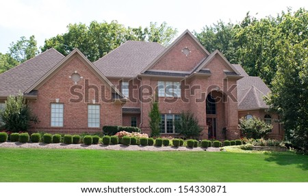 Red Brick House with Shrubs - stock photo