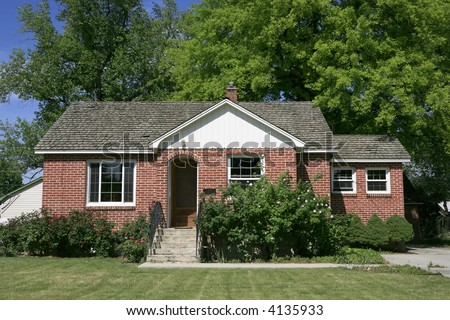 Red brick small home with green tree background - stock photo