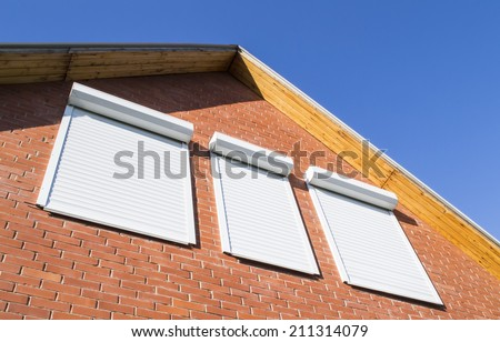Red brick wall and window with rolling shutters - stock photo