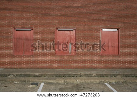 red brick wall boarded windows in parking lot - stock photo