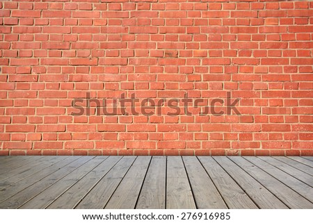 Red brick wall on wooden floor. - stock photo