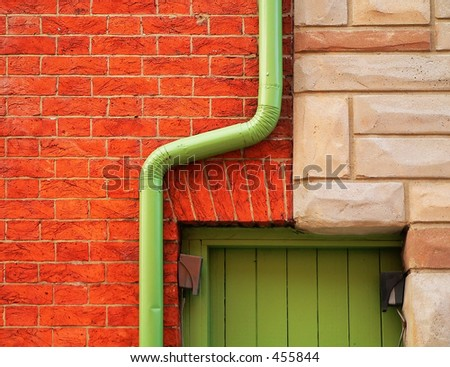red brick wall, rain gutter curves around green door - stock photo
