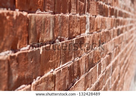 Red brick wall shot with the rows of bricks and grout fading into the distance. - stock photo