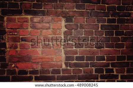 Red brick wall with a hole that is covered with newer bricks. Image has a vintage effect applied.