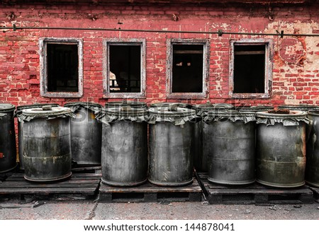 Red brick wall with barrel outdoors - stock photo