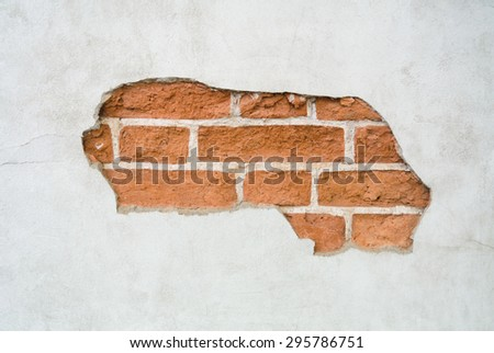 Red brick wall with cracked white plaster or stucco background - stock photo